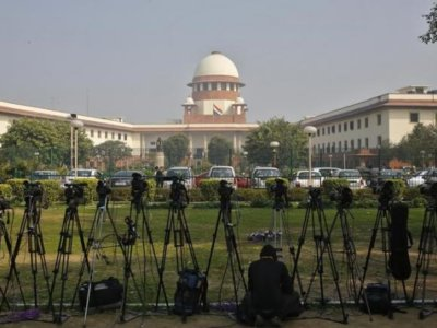 A television journalist sets his camera inside the premises of the Supreme Court in New Delhi February 18, 2014. REUTERS/Anindito Mukherjee/Files