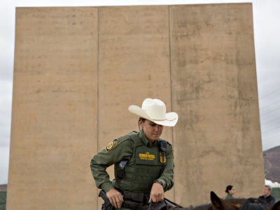 A U.S. Border Patrol agent sits on a horse in front of a U.S.-Mexico border wall prototype while patrolling in San Diego on Oct. 30. MUST CREDIT: Bloomberg photo by Daniel Acker