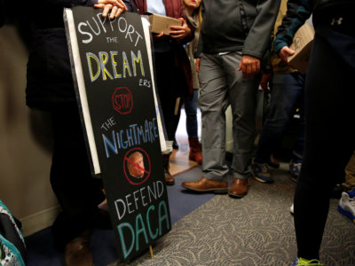 Protesters calling for an immigration bill addressing the so-called Dreamers, young adults who were brought to the United States as children, carry a sign supporting DACA in the office of Senator Chuck Grassley on Capitol Hill in Washington, U.S., January 16, 2018. REUTERS/Joshua Roberts