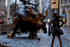 A statue of a girl facing the Wall St. Bull is seen, as part of a campaign by U.S. fund manager State Street to push companies to put women on their boards, in the financial district in New York, U.S., March 7, 2017. REUTERS/Brendan McDermid/File Photo