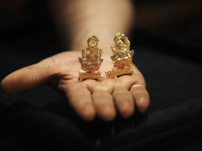 A worker at a jewellery showroom displays gold idols of Hindu elephant god Ganesh (L) and Hindu goddess Lakshmi in Kolkata August 30, 2013. REUTERS/Rupak De Chowdhuri/Files