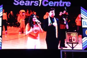 Seen on the jumbotron, Ashley Singh performs the U.S. national anthem Feb. 12, as FIA founder and President Sunil Shah, stands beside her, at the Sears Center Arena, Chicago, during a basketball game, where the Federation of Indian Associations celebrated Indian Heritage Night. (Photo: Adbhut Media)