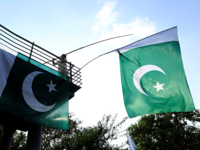 A boy uses a bamboo stick to adjust national flags at an overhead bridge ahead of Pakistan's Independence Day, in Islamabad, Pakistan August 10, 2018. REUTERS/Faisal Mahmood