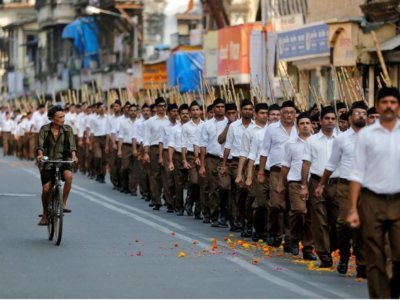 """A man rides his bicycle past volunteers of the Hindu nationalist organisation RSS taking part in the """"Path-Sanchalan"""", or Route March during celebrations to mark the Vijaya Dashmi or Dussehra in Mumbai, India October 11, 2016. REUTERS/Shailesh Andrade/File Photo"""
