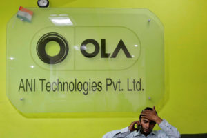 An employee speaks over his phone as he sits at the front desk inside the office of Ola cab service in Gurugram, on the outskirts of New Delhi, April 20, 2016. REUTERS/Anindito Mukherjee/Files