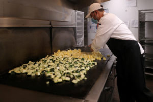 A chef cooks vegetables at the Westin Bonaventure hotel as part of California Governor Gavin Newsom's program to use FEMA and local money to produce meals to deliver to at-risk seniors, as the global outbreak of the coronavirus disease (COVID-19) continues, in Los Angeles, California, U.S., May 7, 2020.  REUTERS/Lucy Nicholson