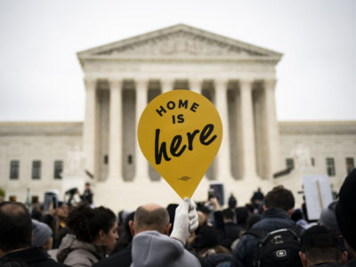 """A demonstrator holds a """"Home Is Here"""" sign during a rally supporting the Deferred Action for Childhood Arrivals program (DACA) outside of the Supreme Court in Washington, D.C., U.S., on Nov. 12, 2019. MUST CREDIT: Bloomberg photo by Al Drago"""