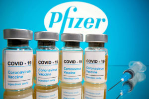 "Vials with a sticker reading, ""COVID-19 / Coronavirus vaccine / Injection only"" and a medical syringe are seen in front of a displayed Pfizer logo in this illustration taken October 31, 2020. REUTERS/Dado Ruvic/File Photo"