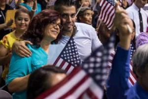 David Reyna hugs his mother, Tina Chavez, originally from Mexico, as she participates in the Fiesta of Independence Naturalization Ceremony at South Mountain Community College in Phoenix on July 4, 2018. MUST CREDIT: Washington Post photo by Carolyn Van Houten.