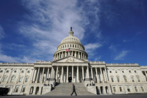 FILE PHOTO: A man makes his way past the U.S. Capitol on the day the House of Representatives is expected to vote on legislation to provide $1.9 trillion in new coronavirus relief in Washington, U.S., February 26, 2021. REUTERS/Kevin Lamarque/File Photo