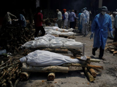 FILE PHOTO: A health worker wearing personal protective equipment (PPE) walks past the funeral pyres of those who died from the coronavirus disease (COVID-19) during a mass cremation at a crematorium in New Delhi, India, April 26, 2021. REUTERS/Adnan Abidi/File Photo