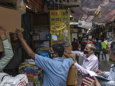 People stand in front of a store at the Bhagirath Palace wholesale medicine market in New Delhi on May 5, 2021. MUST CREDIT: Bloomberg photo by Sumit Dayal.